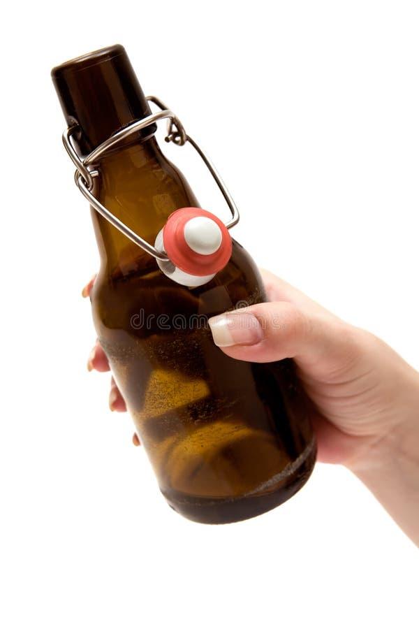 Tenir une bouteille de bière photo stock
