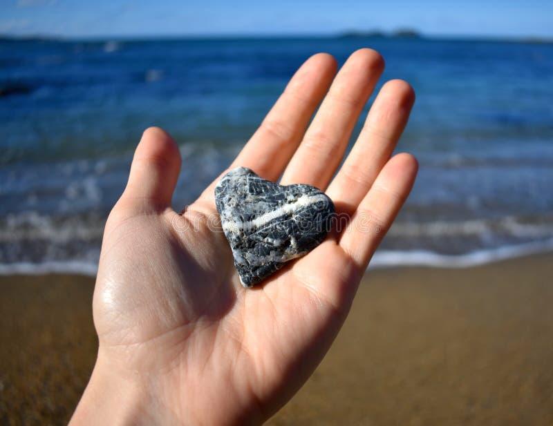 Tenir une roche en forme de coeur image libre de droits