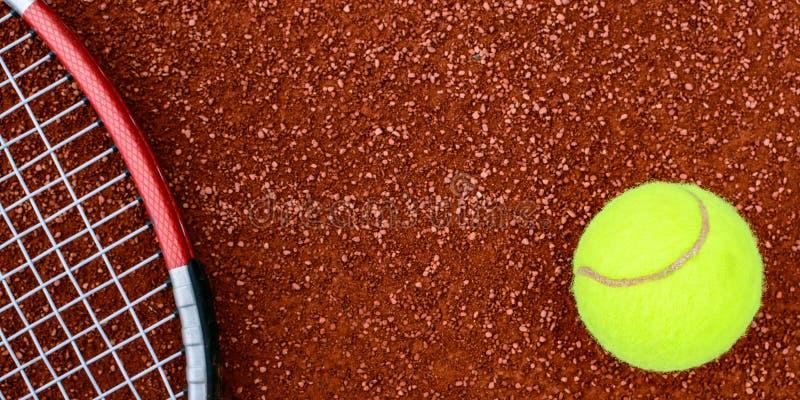 Tenisowa piłka i racquet na glinianym sądzie zdjęcia royalty free
