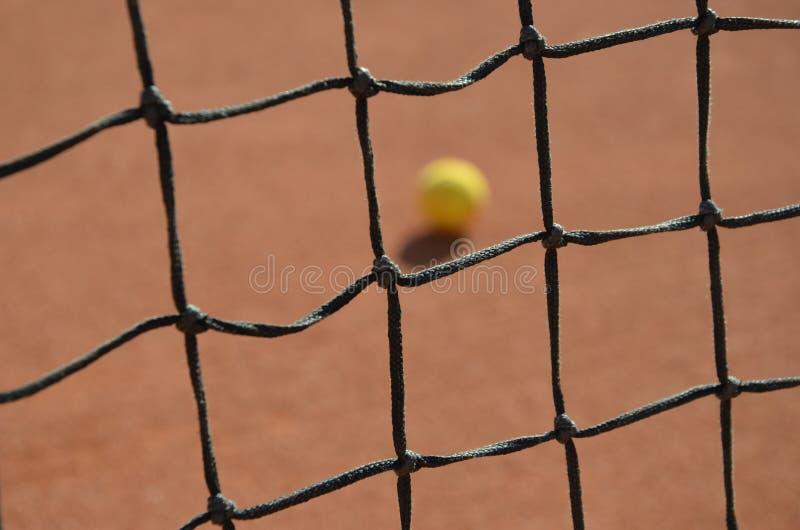 Tenisowa piłka zamazywał fotografię przez tenisowej sieci obraz stock