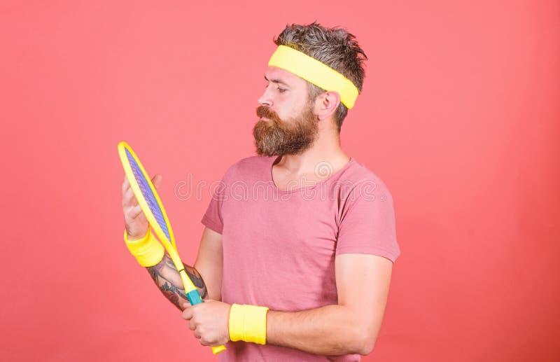 Tenisowy sport i rozrywka Atleta modnisia chwyta tenisowy kant w r?ki czerwieni tle Sztuka tenis dla zabawy cz?owieku fotografia royalty free