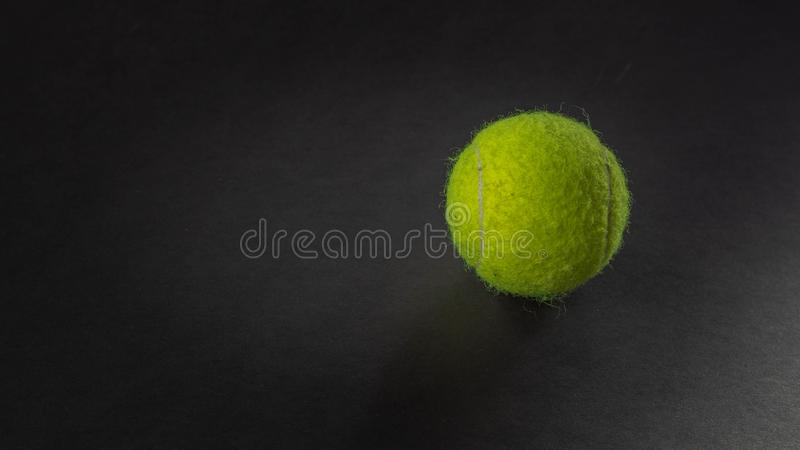 Tennis ball on black background royalty free stock photography