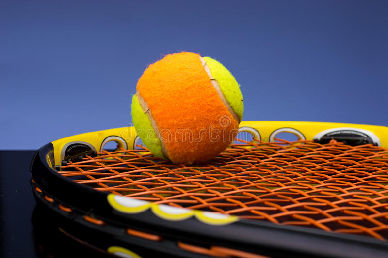 Tennis ball for children with tennis racket. Tennis ball for kids with tennis racket with green grip handle and orange strings on blue background stock photography