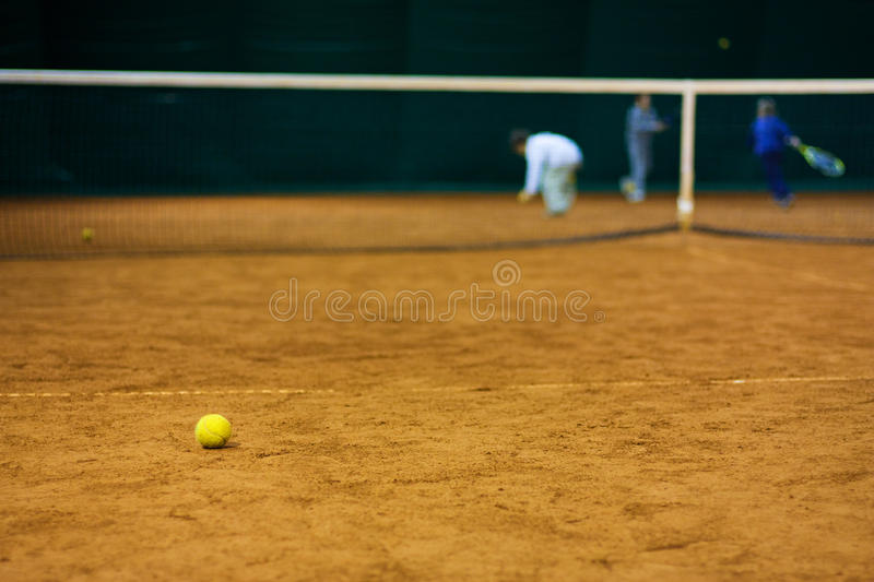 Tennis ball on court. And kids in background More TENNIS and sport here: SPORT royalty free stock image