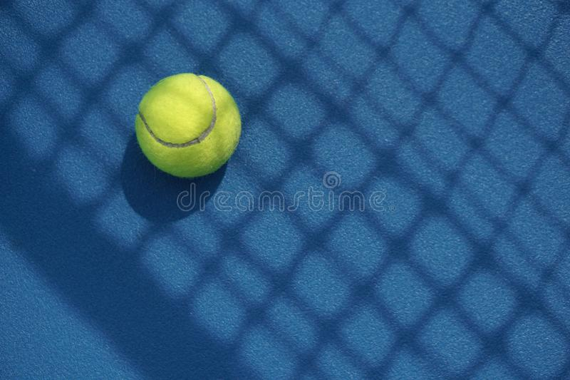 Tennis ball in the court with net shadow on it stock photo