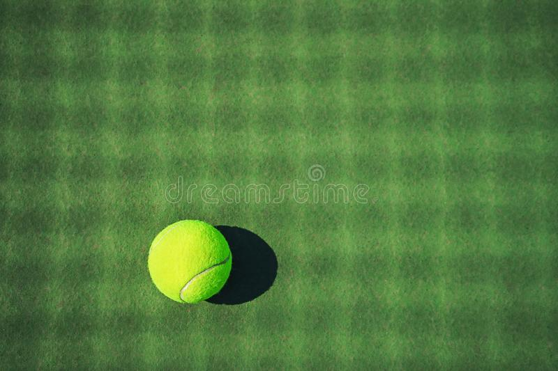 Tennis ball on the green court with net shadows royalty free stock photo