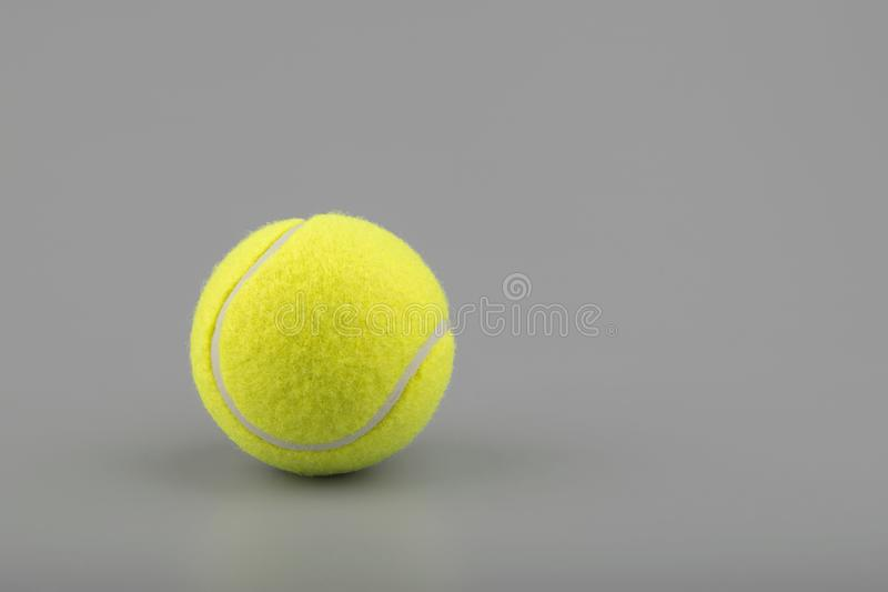 Tennis ball on grey background royalty free stock photography