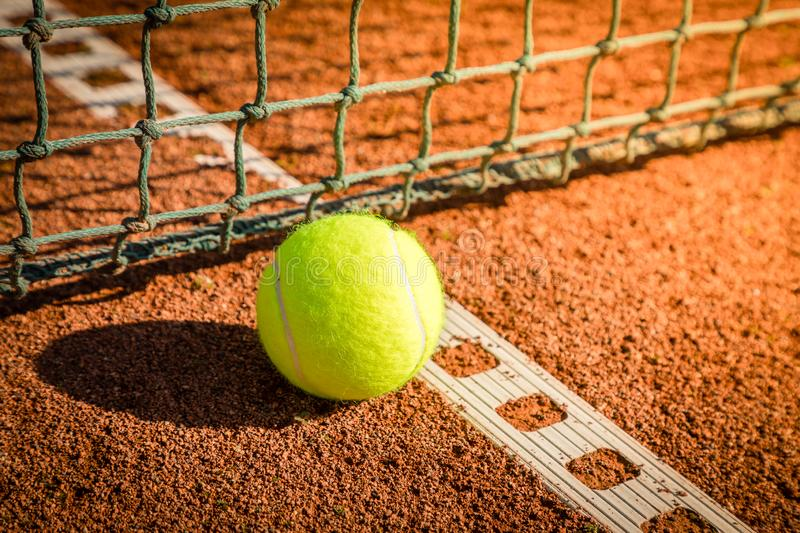 Tennis ball with line on a sand court. Yellow tennis ball with line and ner on a sand court stock photography