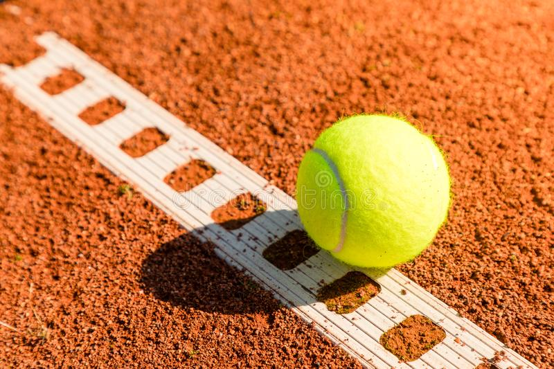 Tennis ball with line on a sand court. Yellow tennis ball with line on a sand court in summer royalty free stock images