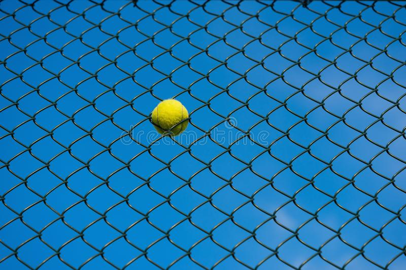 Tennis ball on metal wire against blue sky. Concept of tennis protection equipment stock images
