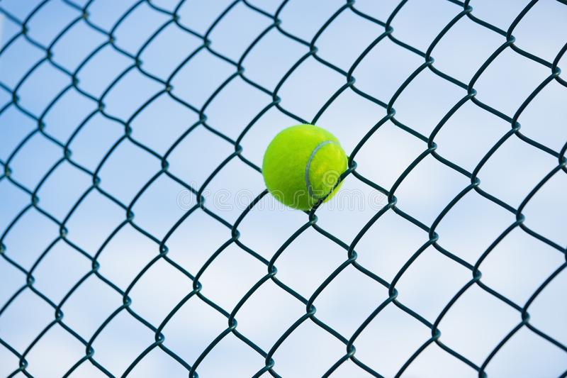Tennis ball on metal wire against sky. Concept of tennis protection equipment stock photography