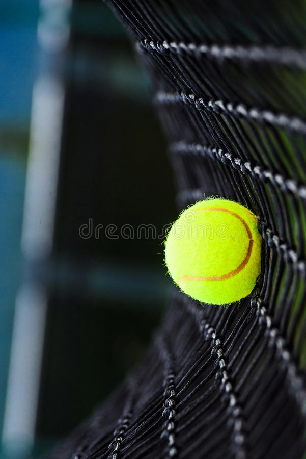 Tennis ball in net. Activity, athletics, background, balls, black, close, closeup, competition, competitive, concept, court, equipment, exercise, fitness, game stock photo