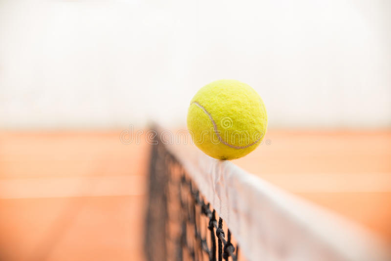 Tennis ball on the net. Tennis ball hitting the net royalty free stock image