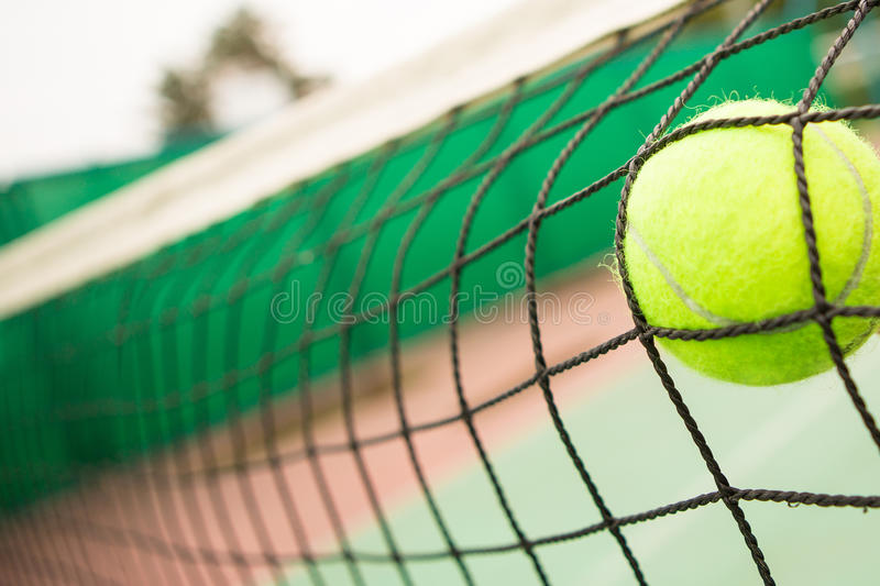 Tennis ball in net stock images