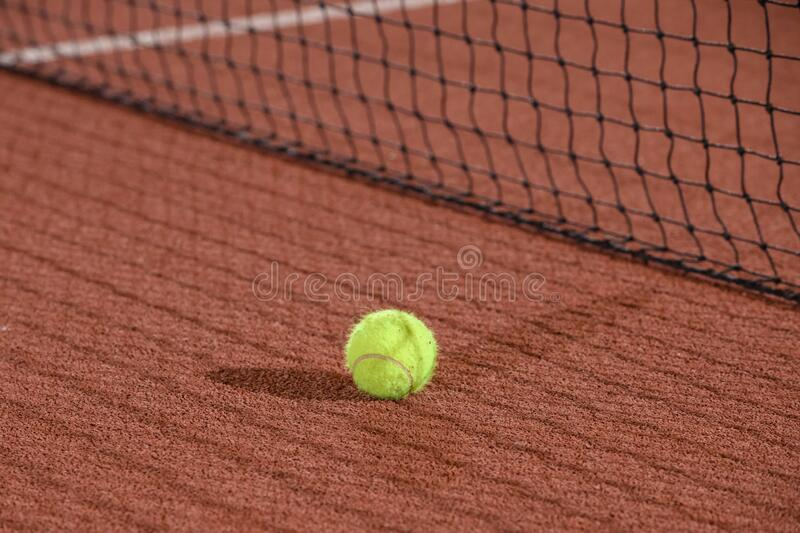 Tennis ball next to the net shot with a shallow depth of field on a clay court royalty free stock images