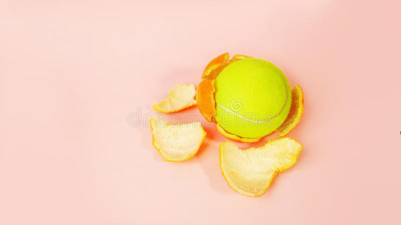 Tennis ball in an orange, concept on tpastel pink background. stock photography