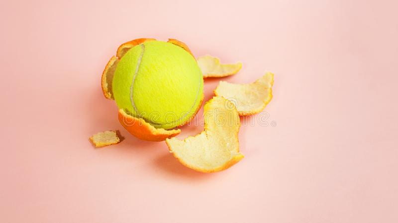 Tennis ball in an orange, concept on trendy pink coral background. royalty free stock image