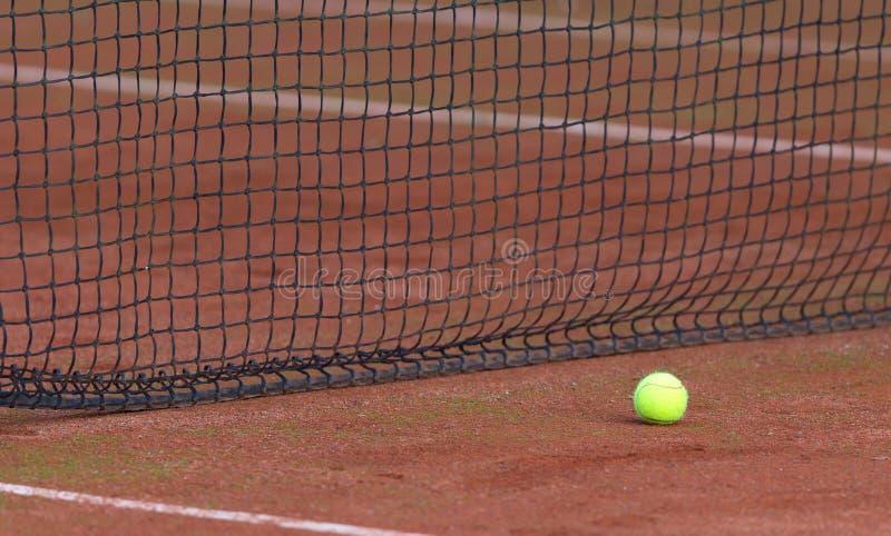 Tennis ball on the orange tenniscourt royalty free stock photo