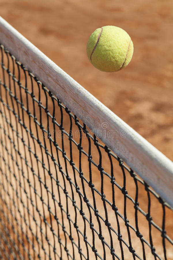 Tennis ball over the net. Close up photograph of a tennis ball passing over the net royalty free stock image