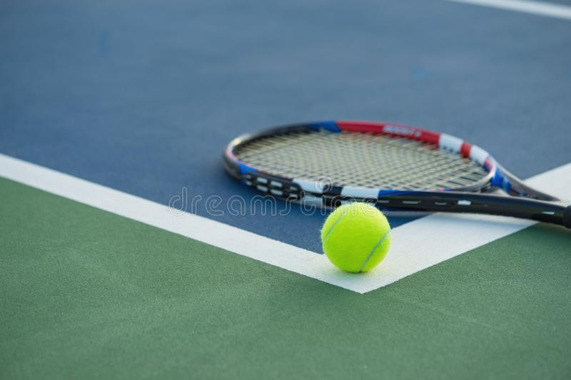 Tennis ball and racket on tennis court royalty free stock photos
