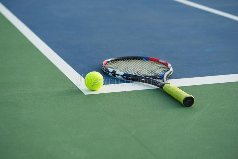 Tennis ball and racket on tennis court stock photography