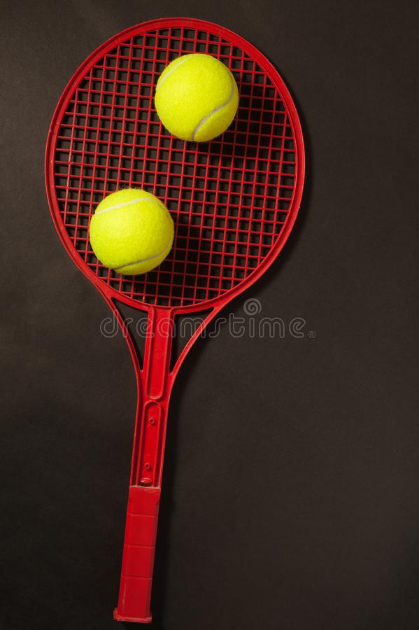 Two tennis ball and racket. Tennis ball and racket on dark background stock images