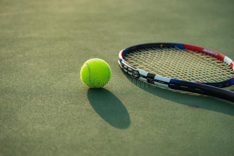 Tennis ball and racket under late evening sunlight royalty free stock photos