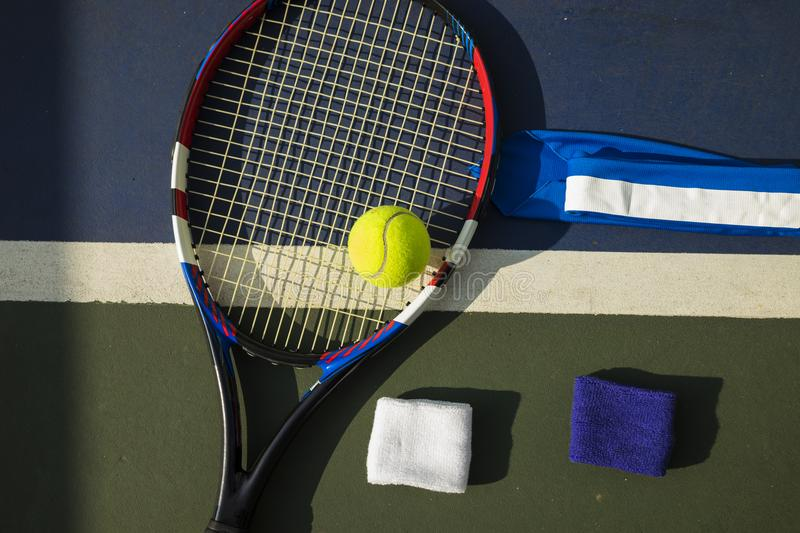 Tennis ball, racket, wristbands on tennis court royalty free stock images