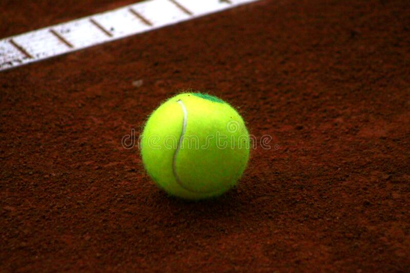 Tennis ball on red background royalty free stock photography