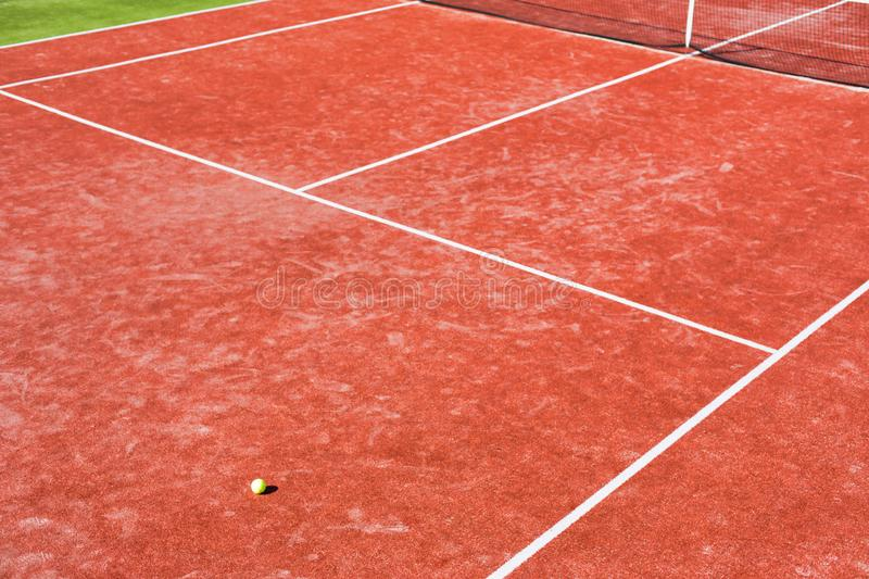 Tennis ball on red court during sunny day. Photo of Tennis ball on red court during sunny day royalty free stock photos