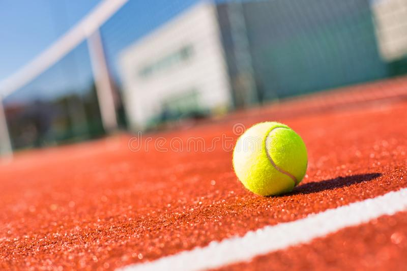 Tennis ball on red court during sunny day. Photo of Tennis ball on red court during sunny day royalty free stock image