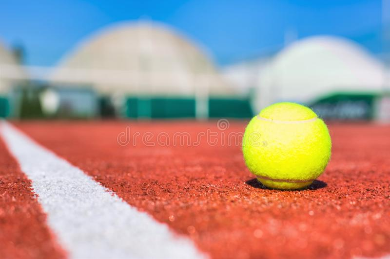 Tennis ball on red court during sunny day. Photo of Tennis ball on red court during sunny day stock image
