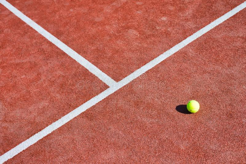 Tennis ball on red court during sunny day. Photo of Tennis ball on red court during sunny day royalty free stock photography