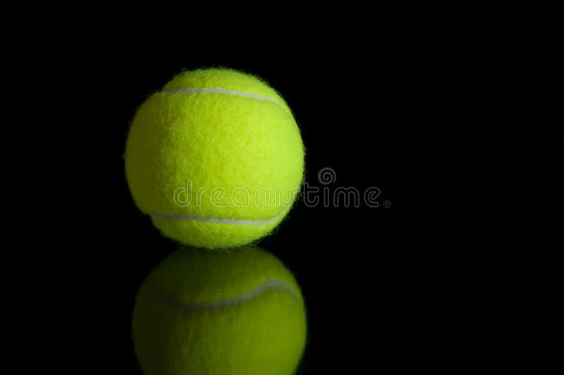 Tennis ball with reflection. Isolated on black background stock images