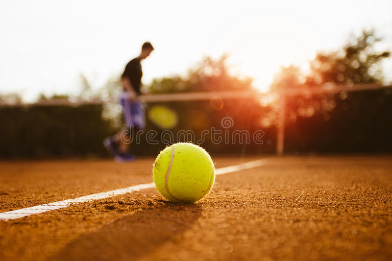 Tennis ball and silhouette of player on a clay court.  stock photography
