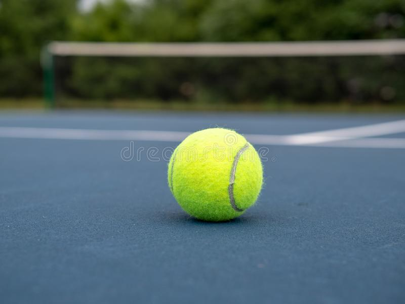 Tennis ball sitting on blue local tennis court with view close to ground. Tennis ball sitting on blue local tennis court with viewpoint close to ground stock photography