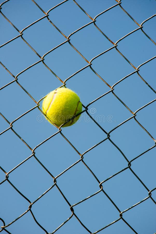 Tennis ball stuck in steal wire net vertical shot royalty free stock images