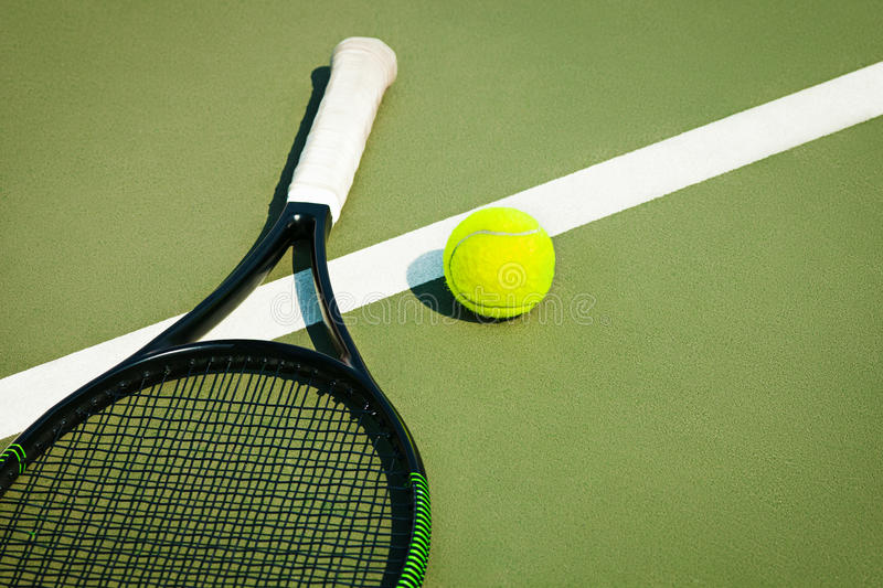 The tennis ball on a tennis court. The green tennis ball on a tennis court stock photography