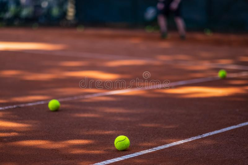 Tennis balls on a court in the foreground. Person blurred in the royalty free stock image