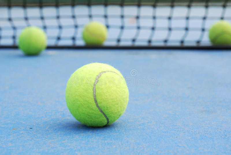 Tennis balls on court with net stock photos