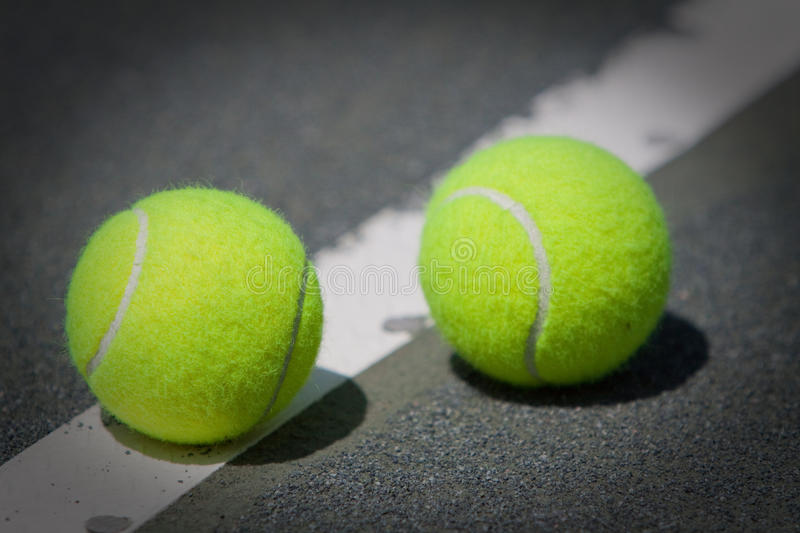 Tennis Balls on Har-Tru clay tennis court. Two tennis balls sitting on the line of a green Har-Tru clay tennis court royalty free stock images