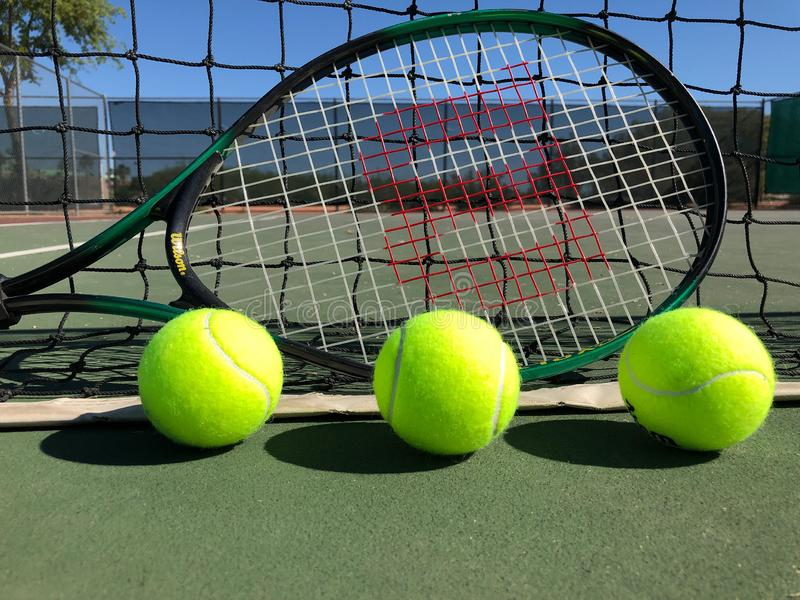 Tennis Balls With Racket. Tennis balls sitting on a tennis racket on the floor of the tennis court stock photo