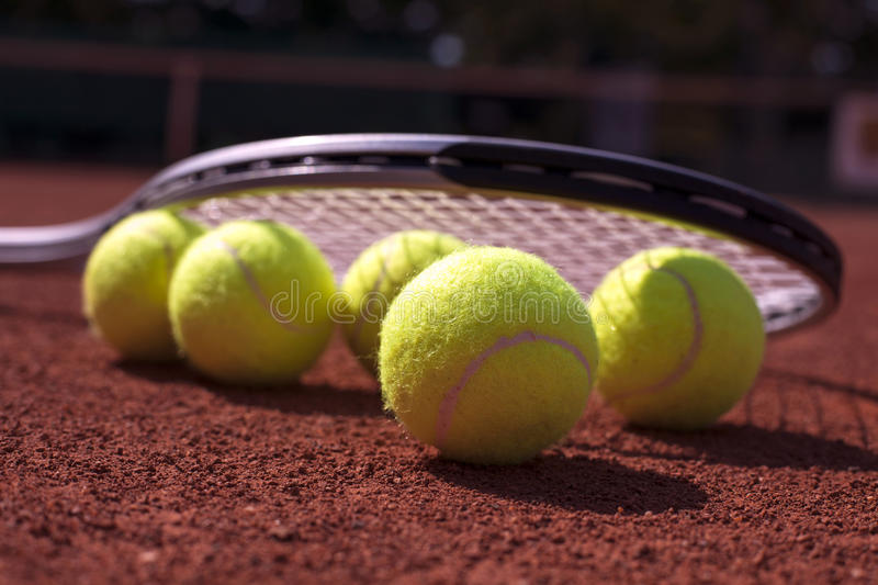 Tennis balls and rocket on court field royalty free stock images
