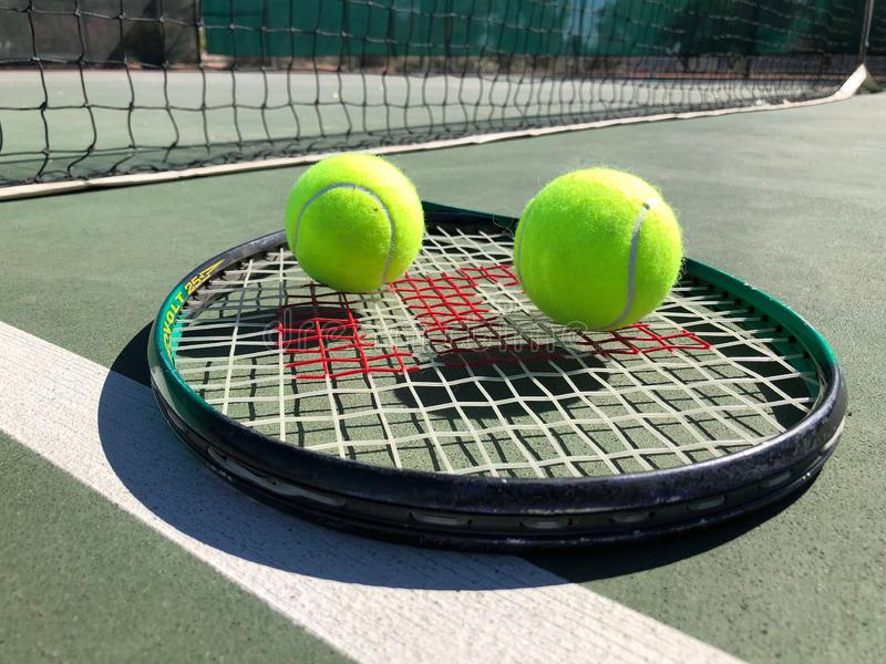 Tennis Balls With Racket. Tennis balls sitting on a tennis racket on the floor of the tennis court stock images