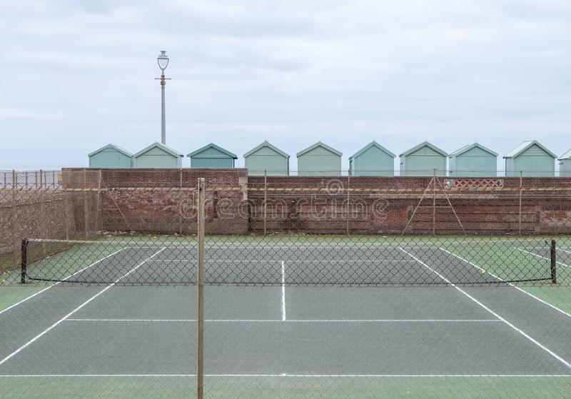 Tennis court, with row of green beach huts behind, on the sea front in Hove, Sussex, UK. Tennis court, with row of green beach huts behind, on the sea front in stock photo