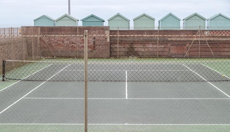 Tennis court, with row of green beach huts behind, on the sea front in Hove, Sussex, UK. Tennis court, with row of green beach huts behind, on the sea front in royalty free stock photos