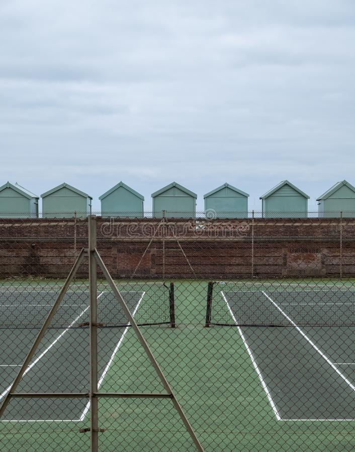 Tennis courts, with row of green beach huts behind, on the sea front in Hove, Sussex, UK. Tennis courts, with row of green beach huts behind, on the sea front in stock image