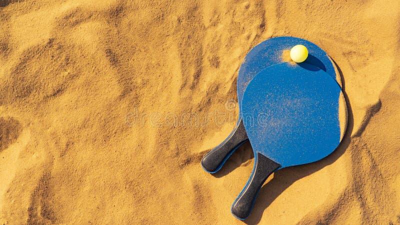 Tennis de raquette et de plage de boule sur le sable d'or images stock