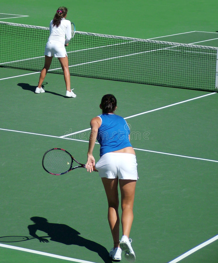 Tennis Doubles Serve & Volley. View of a team of female doubles players - serve and volley point stock photos