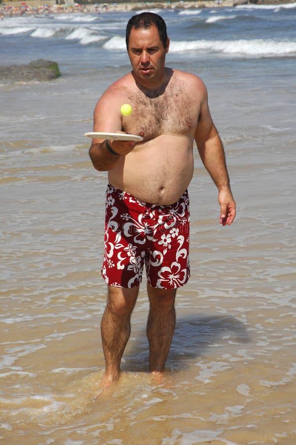 tennis för fet man för strand leka royaltyfri foto